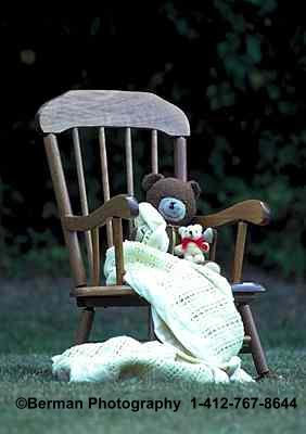Brown Teddy Bear in a rocking chair holding a Baby Bear