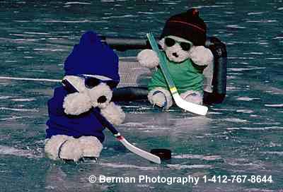 Two ice hockey Teddy Bears shooting at the goal.