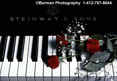 Steinway Piano with a bouquet of red roses.
